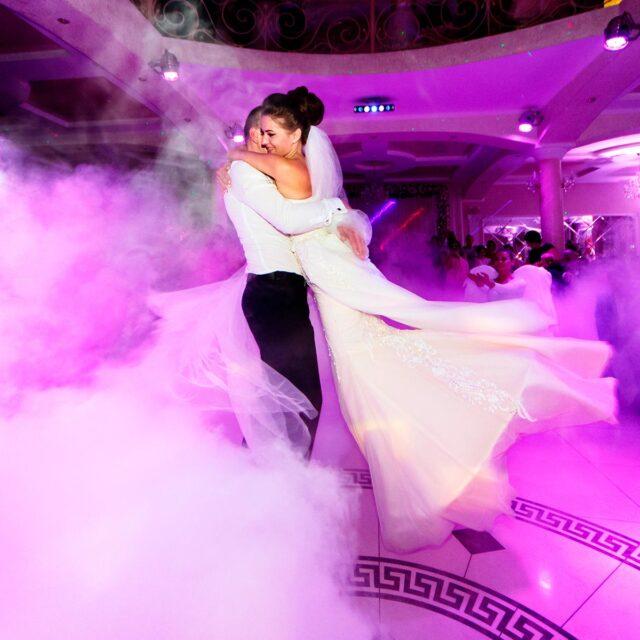 Durante el baile nupcial, envueltos de humo, el novio levanta a la novia y ambos giran en espiral. Una escena que no debe perder un fotógrafo de bodas profesional.