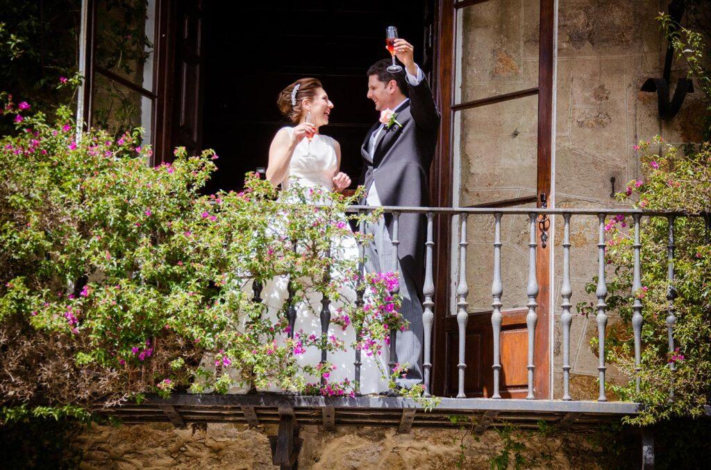 Pareja de novios en actitud radiante que ofrecen un brindis a sus invitados desde el balcón de la finca.
