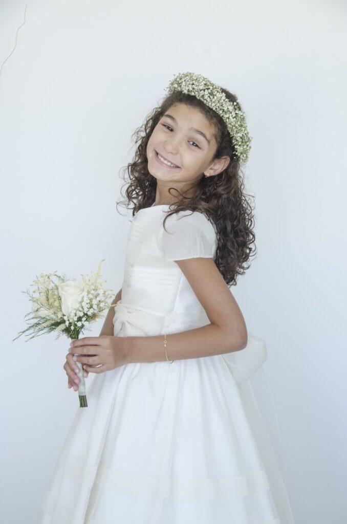 Foto de Comunión de niña con una sonrisa radiante y encantadora. Sostiene un ramito entre sus manos y adorna su pelo con una corona de flores.