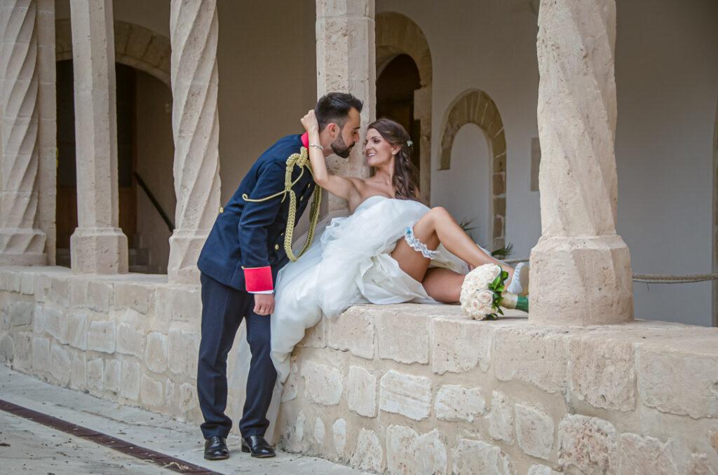 Reportaje en Palma repleto de fotos de boda creativas. En esta imagen, la novia acerca con su brazo al novio vestido de militar. La novia está sentada sobre un muro y enseña la liga en su pierna.