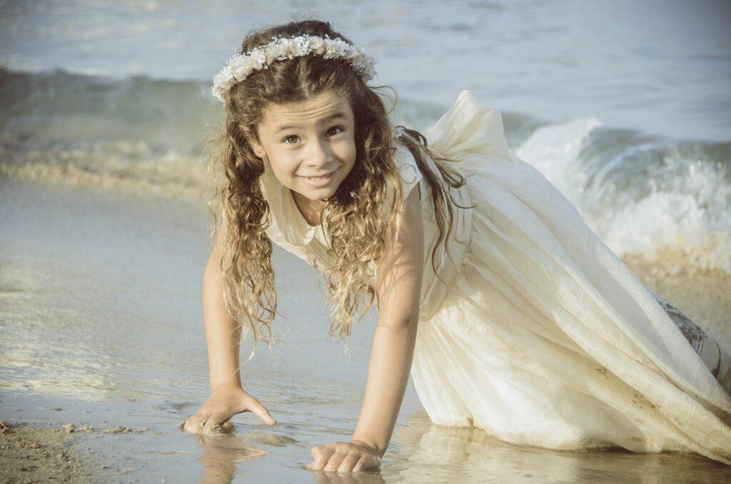 Fotos de Comunión originales en la playa del Coll d'en Rabassa. Esta niña se divierte en la orilla de la playa y sonríe con pillería al fotógrafo.