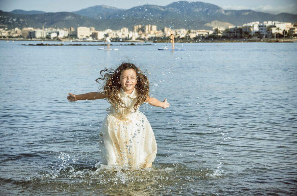 Fotos de Comunión Originales en la Playa. Imagen de niña de comunión que salpica el agua de manera apasionada.