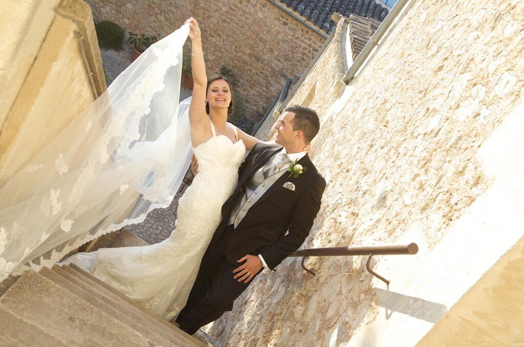 Imagen de una pareja de novios que suben la escalera en el Museu d'Història De Manacor. La chica se para y estira el velo, ante la mirada estupefacta del novia. Esta es una de las muchas fotos de boda creativas captadas este día.