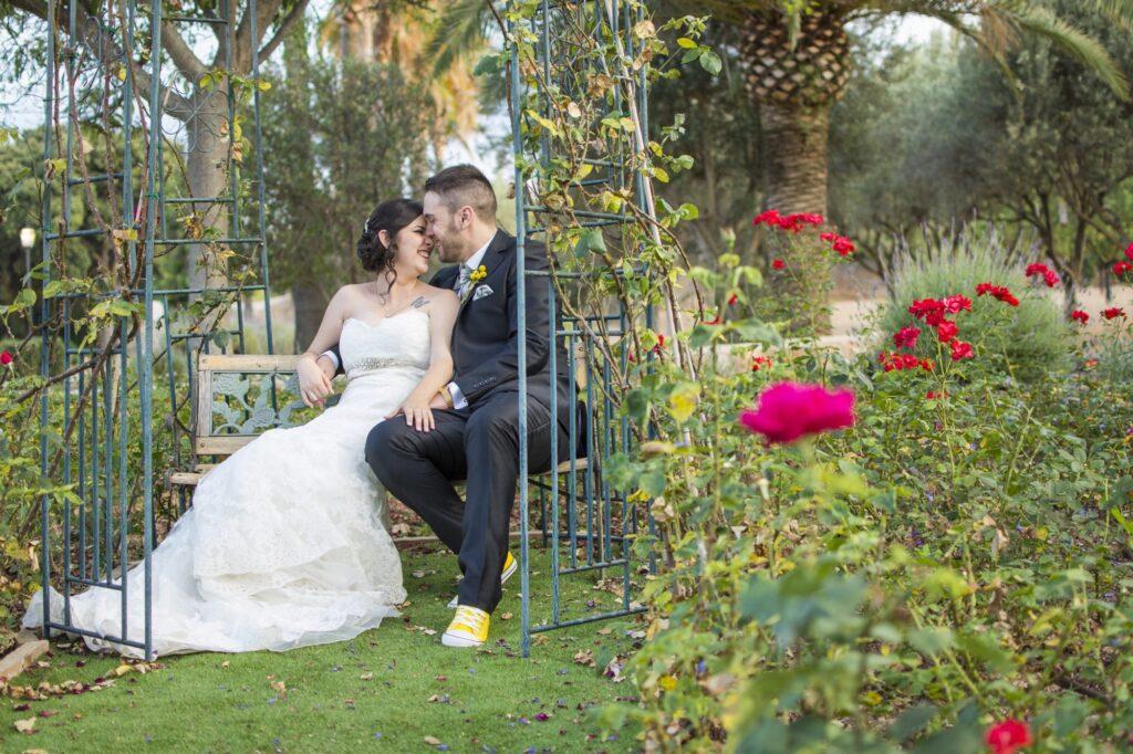 Fotos de Boda Creativas en Son Amar. Jugando con el encuadre y el entorno, se consigue resaltar las rosas rojas en primer plano que conducen la mirada hacia los novios.