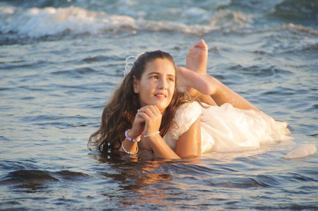 Fotos de Comunión Creativas y Originales en la playa. Soberbia y preciosa imagen de esta niña de comunión tumbada sobre el agua de mar a modo de manto azulado.