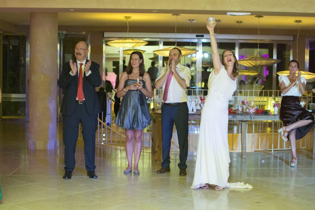 Fotos de boda originales y divertidas en este final de fiesta. La novia levanta su copa con júbilo para brindar con los invitados.