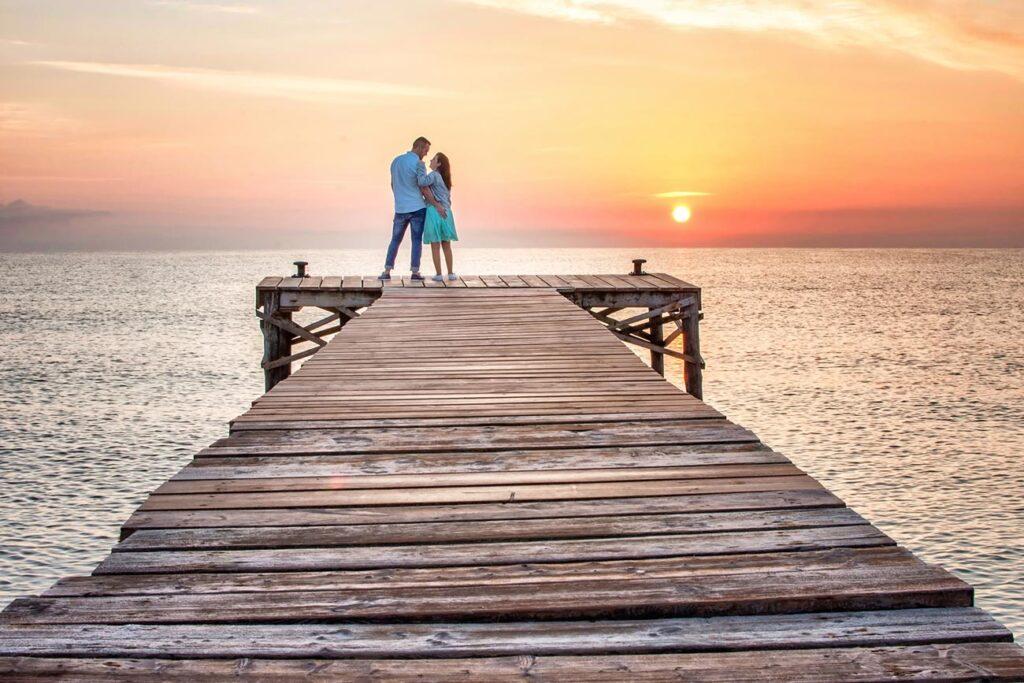 Una pareja de enamorados disfruta del amanecer en un embarcadero de madera al norte de Mallorca. Este tipo de imágenes contribuyen sobremanera a producir únicos y Originales Reportajes de Boda.