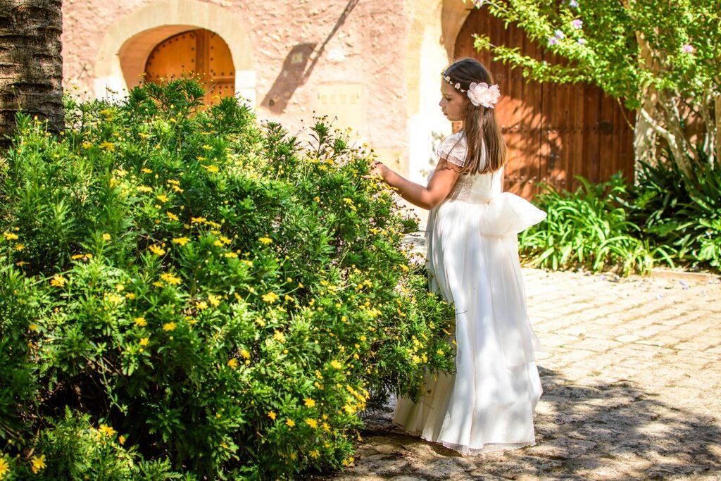 Niña en el día de comunión se deleita con las florecillas de un arbusto en la aldea rústica de Biniagual. Escena de reportajes de comunión en ambiente bucólico