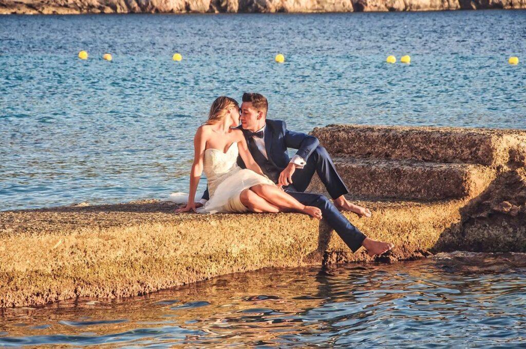 Sobre un embarcadero de piedra, una pareja de novios representan una escena romántica al atardecer. La chica, sentada junto al chico de manera informal, gira levemente el cuello para situar sus labios cercanos a los de el novio, apenas besándose. Foto de reportaje post boda original y encantadora en la playa de Camp de Mar.