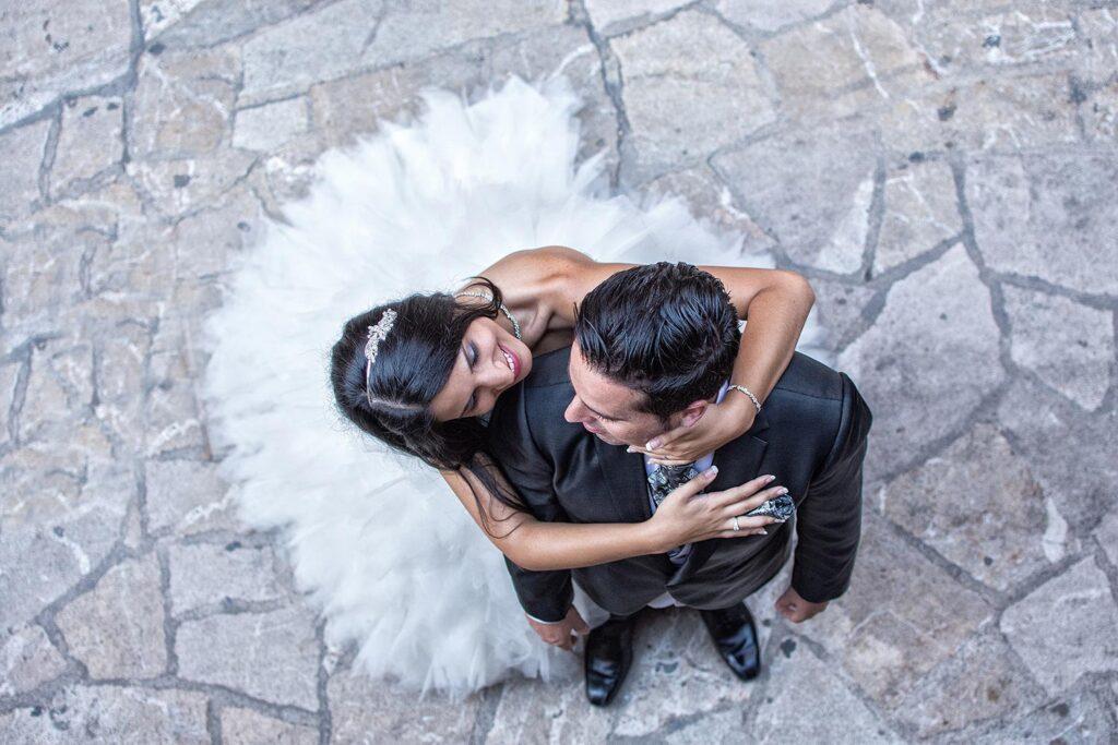 Imagen de Boda Original con punto de vista elevado donde la novia abraza al novio sobre suelo con textura