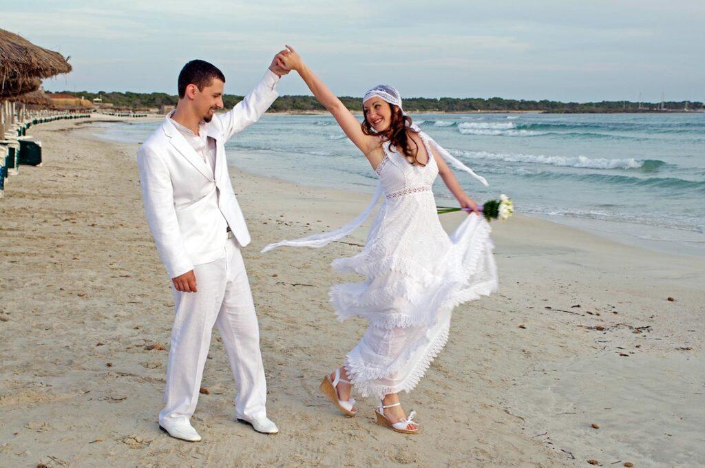 Fotos de boda creativas al lado del mar. Novios radiantes muestran su felicidad mientras se divierten en la playa.. Ambos se cogen de la mano y sin soltarse, la chica describe una figura típica de coreografía de baile, la cual dedica a su esposo. Fotografías originales de boda en entornos idílicos de Mallorca.