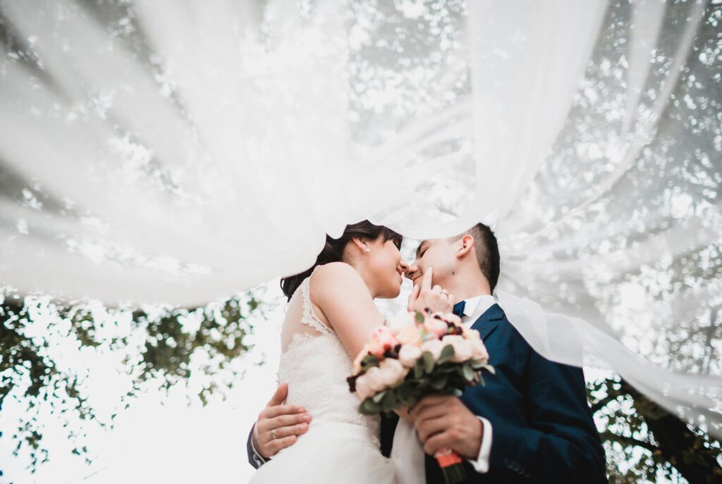 Fotografia de boda con un punto de vista muy original. La novia hace arrumavos al novio, que está frente a ella sosteniéndole el ramo. La imagen está captada desde un punto de vista inferior, de manera que el velo de la novia cubre al fotógrafo y guía la vista hacia la pareja de recién casados.