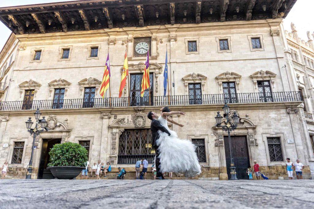 Fotografía Urbana donde el novio eleva a la novia frente al Ayuntamiento de Palma. Foto por Francisco Torralbo, fotógrafo de bodas en Mallorca