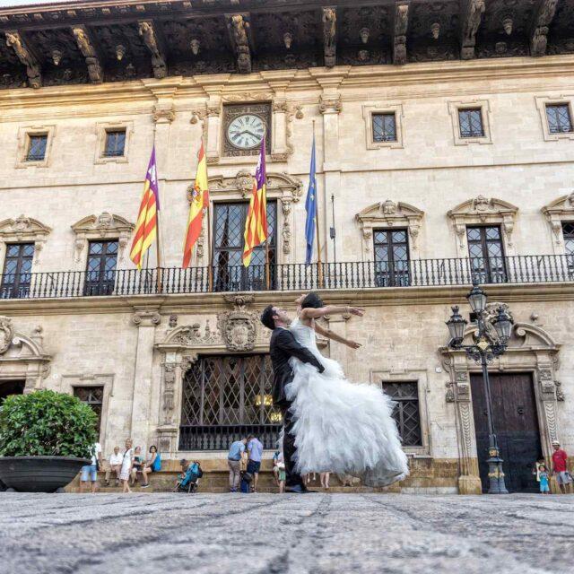 Fotografía Urbana donde el novio eleva a la novia frente al Ayuntamiento de Palma