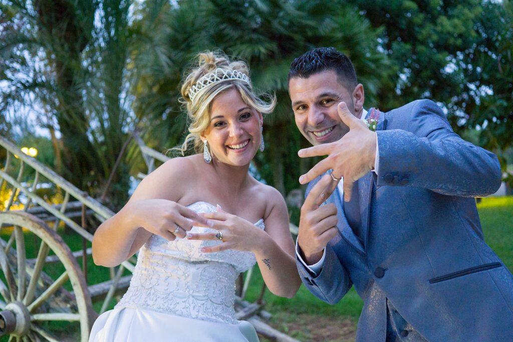 Reportaje de boda muy rico en escenas maravillosas y divertidas. En la imagen se muestra a una pareja de recién casados mostrando con alegría sus anillos con las manos extendidas.