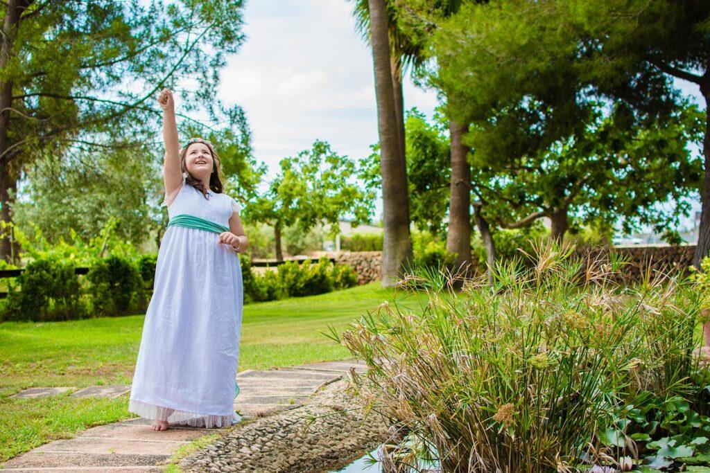 Una niña dedica un gesto entusiasta levantando su brazo derecho en señal de triunfo. A su lado se distingue un estanque y tras de sí se dibuja un jardín con árboles y césped. La escena en este reportaje de comunión sugiere un reto al mundo que invita a la aventura y a la vivencia de historias emocionantes.