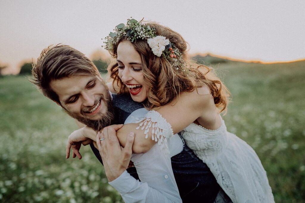 Idílica escena de una pareja de Novios divirtiéndose en un verde prado al atardecer. Ella le atrapa por detrás y hace gesto de subirse a la espalda del chico, mientras él se gira y sonríe.