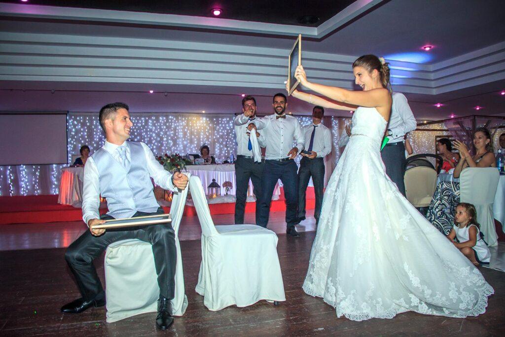 Fotos de boda divertidas de juegos durante la velada. Los amigos de los novios han organizado un trivial de preguntas y respuestas en el que compiten los recién casados. En esta escena la novia enseña la pizarra con la respuesta ganadora.