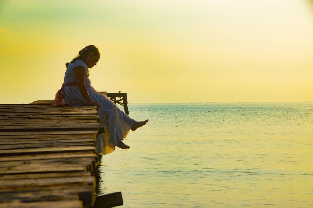 Foto de comunión al norte de Mallorca de una niña sentada en embarcadero