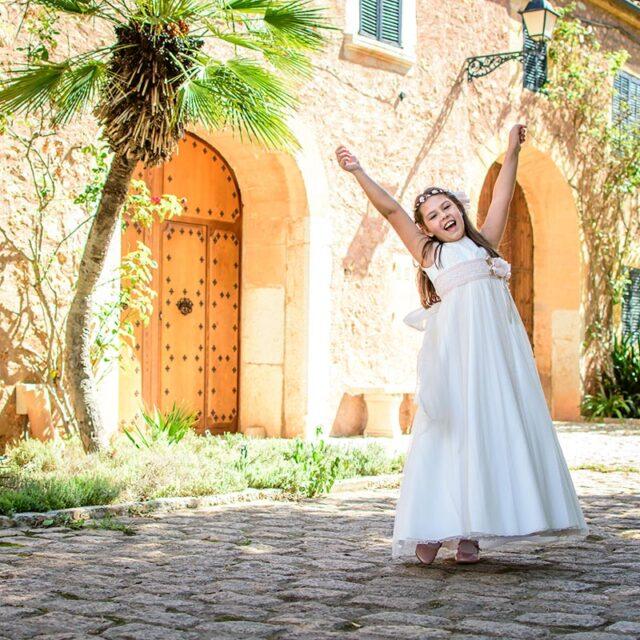 Niña vestida de Comunión se muestra radiante en un entorno rústico. La niña levanta los brazos en señal de júbilo.