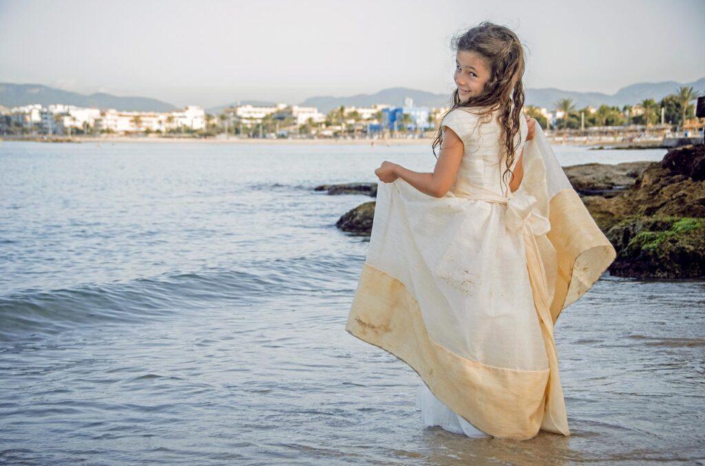 Niña en traje de comunión junto a la orilla del agua en la playa. La pequeña se gira mientras levanta el vestido y dedica miradas repletas de picardía antes de cometer su travesura