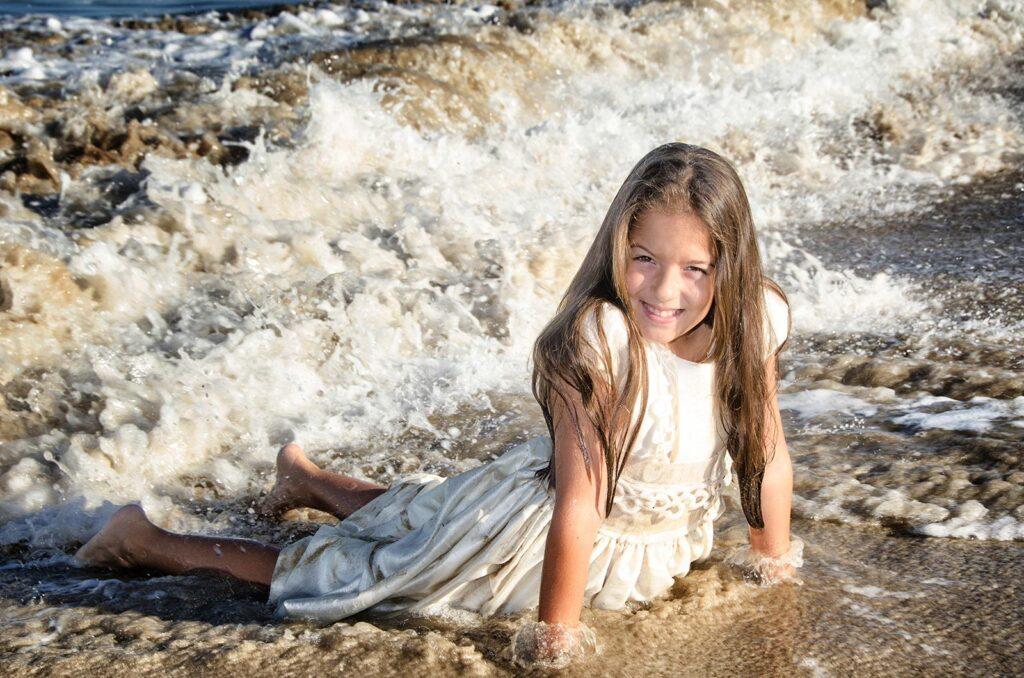 Imagen tomada un segundo antes de que esta pequeña en su traje de comunión sea arroyada por una ola furiosa de agua y arena en la playa del Coll d'en Rabassa. Momentos alegres y divertidos en los reportajes de comunión de nuestros pequeños.