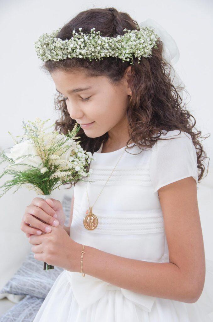 Niña en el día de su comunión se deleita cuando huele el ramito de flores que complementa su traje.