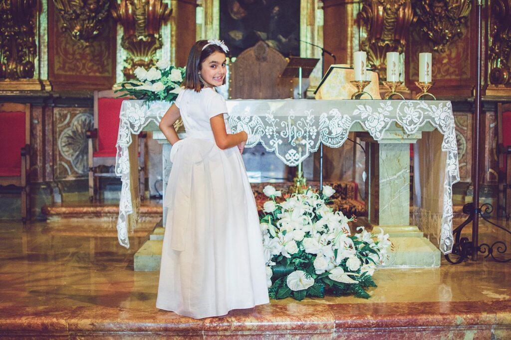 Niña de comunión se luce en el altar de la Iglesia de Sant Marçal. Con una pose muy simpática se gira y enseña el lazo que adorna la parte trasera de su vestido.. Está a punto de iniciar la aventura de su Primera Comunión.