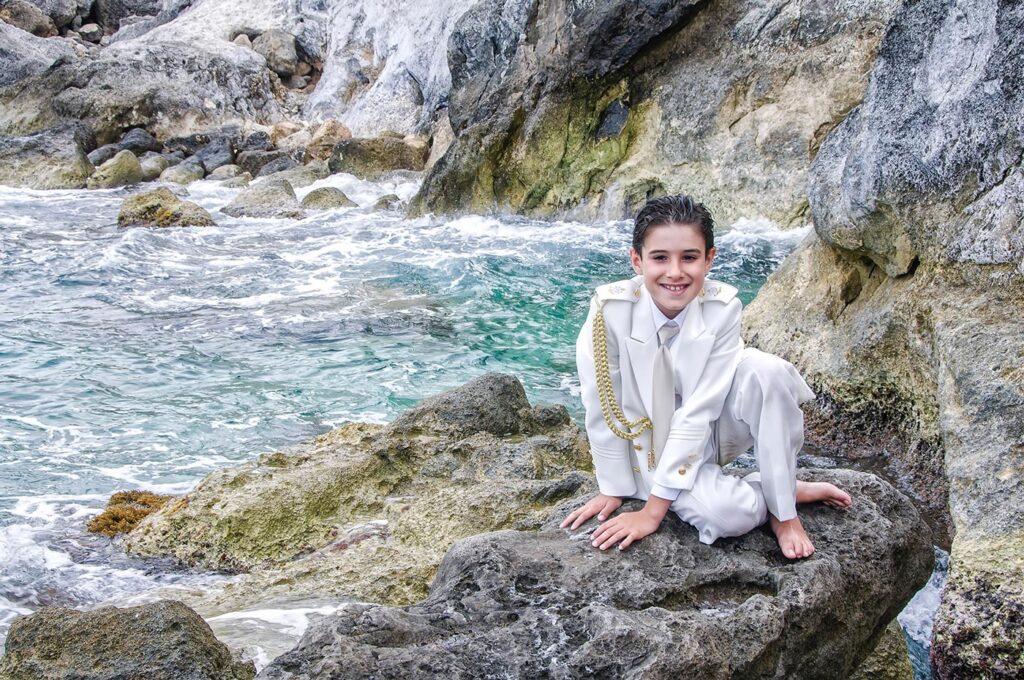 Este niño con traje de comunión posa en una roca al borde de un océano de tonalidades verde azuladas. Las rocas que enmarcan la escena le confieren a la fotografía una atmósfera de fantasía.