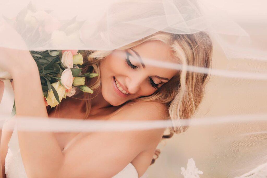 Novia se muestra feliz y con gesto afortunado se acurruca tras su ramo. Escena vista a través del velo que hace de pantalla entre el fotógrafo y la novia. Fotos de novias divirtiéndose en su gran día.