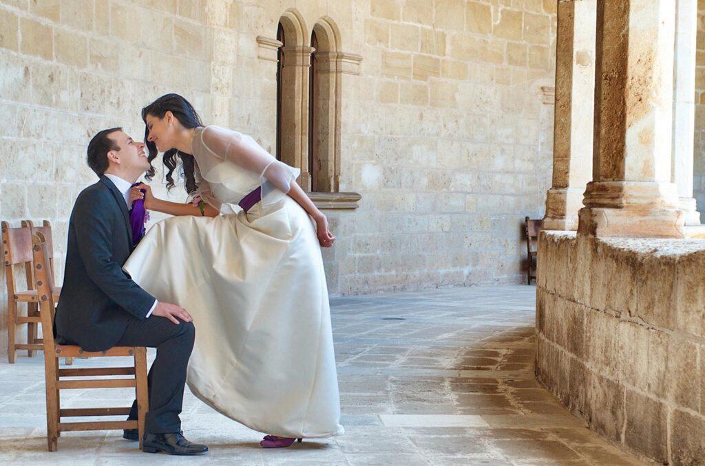 Foto de boda creativa que describe una situación diferente. La novia adopta un papel autoritario frente al novio, que está sentado en una silla. Ella se acerca, apoya una pierna en la silla y le atrae agarrándole por la corbata.
