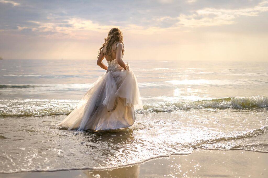 Novia camina en la orilla del mar con su traje de boda