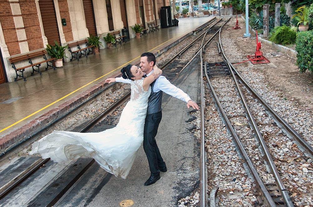 Novia se cuelga del cuello de su novio y ambos giran en la intersección de las vias de la estación
