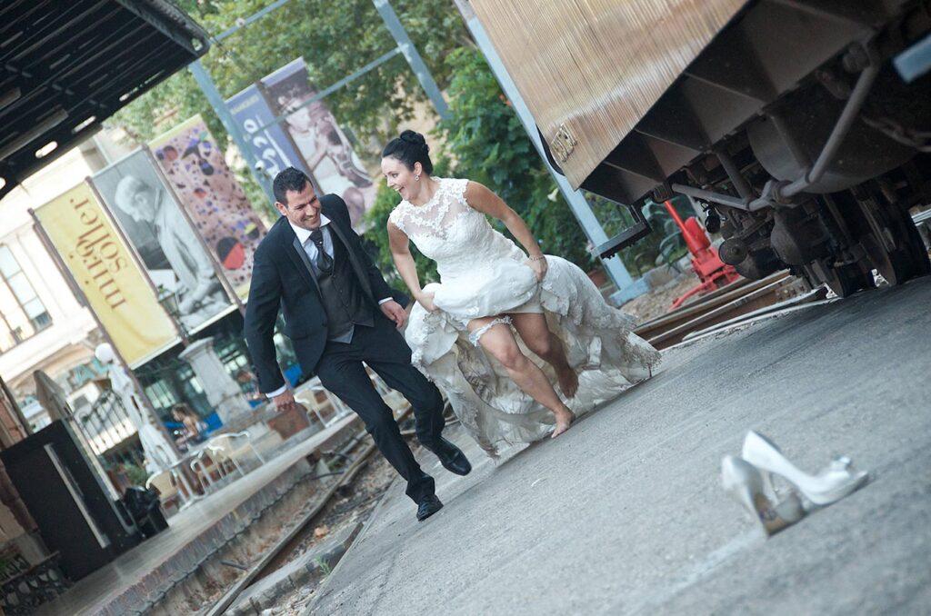 Fotografías de boda insólitas y originales. Aquí se representa una novia feliz que corre descalza junto a su novio en la estación del tren de Sóller en Palma Ciudad. Una manera de resaltar escenarios pintorescos en Fotografía de Boda Urbana
