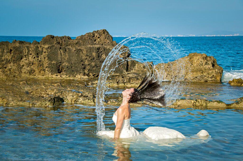 Novia dibuja con su pelo un arco de agua alrededor de su cuerpo. Está de rodillas dentro del agua de azul intenso y cristalino.
