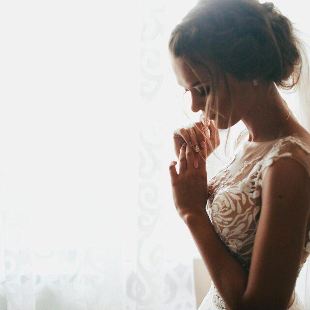 Novia posa con encanto junto a la ventana. El lateral de la chica visible desde el punto de vista del fotógrafo permanece en penunmbra y el resto de la escena queda iluminado en blanco