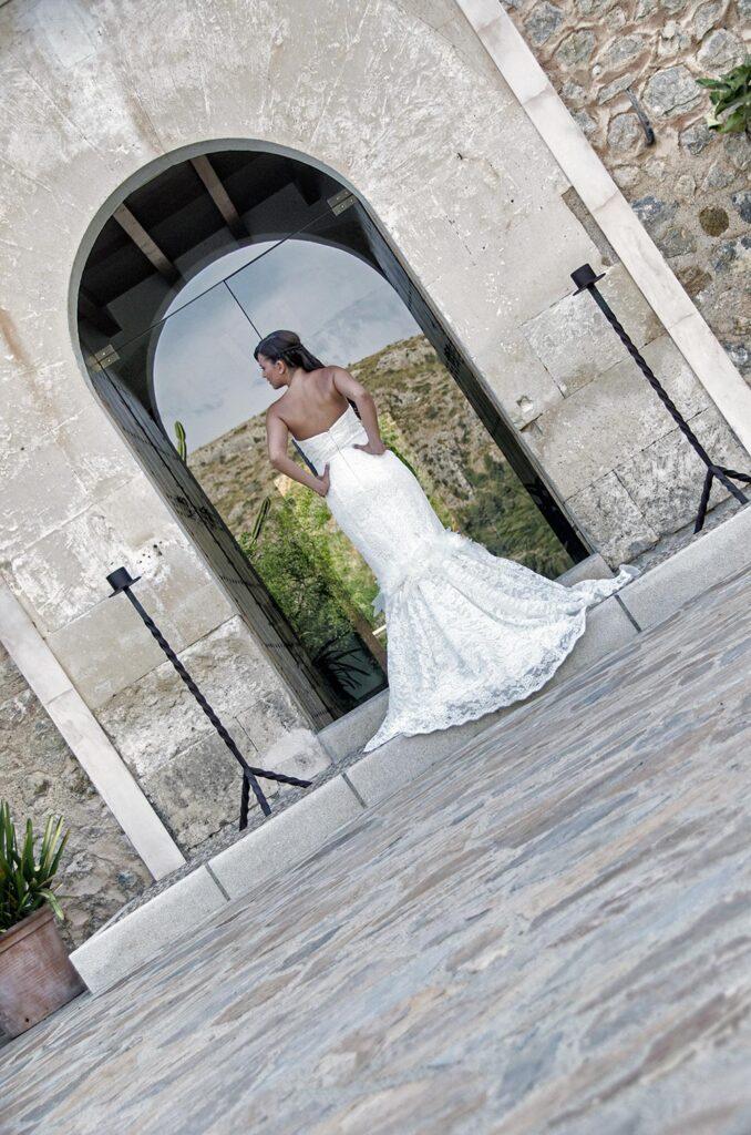 La novia posa con estilo de espaldas al objetivo del fotógrafo. Enfrente de ella hay una puerta con cristal que refleja una montaña que hay en el lado opuesto del edificio. Fotos de Novias con estilo en Son Siurana.