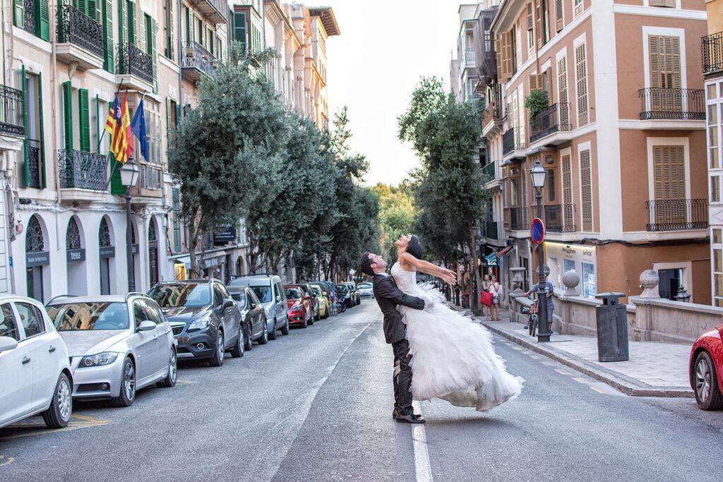 Novia que sorprende realizando una figura cuando el novio la eleva en mitad de la calle. Fotografías de Boda Originales durante un reportaje en Palma.
