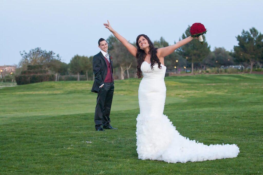 Fotografías Originales de Boda en el Campo de Golf de Son Antem. La novia levanta los brazos al aire con júbilo desmedido. Con cara de felicidad y regocijo mira hacia el cielo, mientras su pareja permanece al fondo sonriendo mirando la figura de su chica.