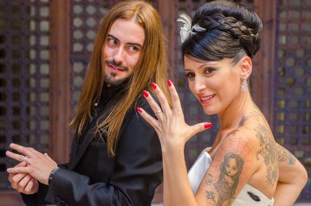 Fotografía de Boda Creativa con mucho encanto en la que la novia muestra con orgullo su anillo con la mano extendida. El novio la mira con asombro, mientras se toca también el anillo.