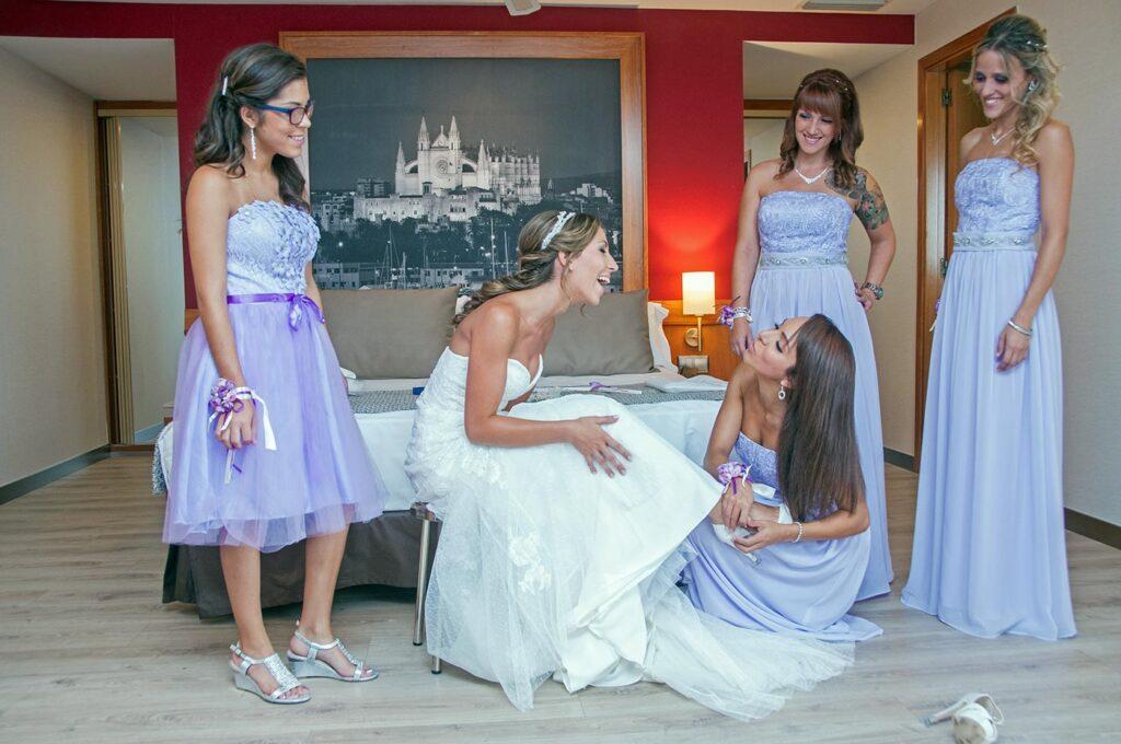 La novia y sus damas de honor ultiman detalles en la habitación del hotel. Una de ellas retoca el zapato de la novia, momento en el que las chicas hacen un gesto gracioso de complicidad. Al fondo destaca un cuadro de la Catedral de Palma.
