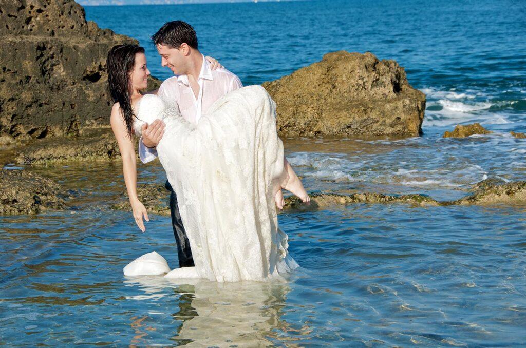 Novio carga a la novia en sus brazos en una cala de rocas. Los novios están dentro de un agua cristalina de color azul intenso. Foto de boda en la playa de Cala Gamba