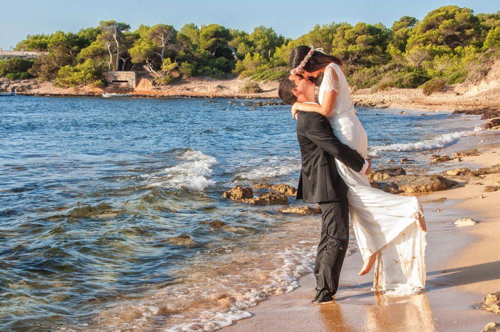 Fotos de Boda Originales en la Playa de s'Estanyol. El novio levanta a la novia en vertical hasta que la cabeza de ella queda ligeramente por encima de la de él, momento en el que sus rostros se acercan de forma romántica.