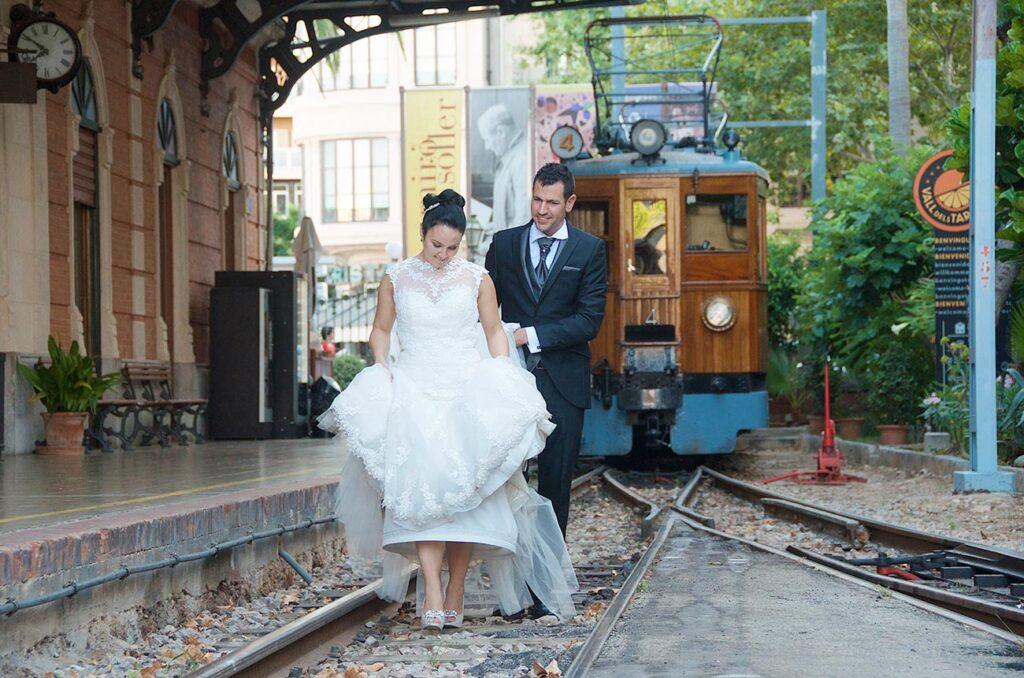 Novios caminan por la via de la estación en la ciudad de Palma. El tren de Sóller de estilo vintage permanece aparcado al fondo. Fotografía de boda con una composición muy cuidada y original.