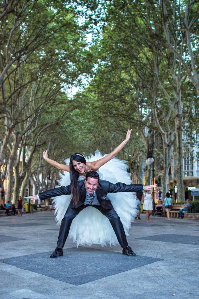 Una pareja de novios se divierten en el Passeig des Born en Palma. Ella se sube con los brazos estirados sobre la espalda del novio, quien se inclina para mantenerla en equilibrio. Una imagen tipo de fotografía original y espontánea dentro de un entorno de Fotografía de Boda Urbana