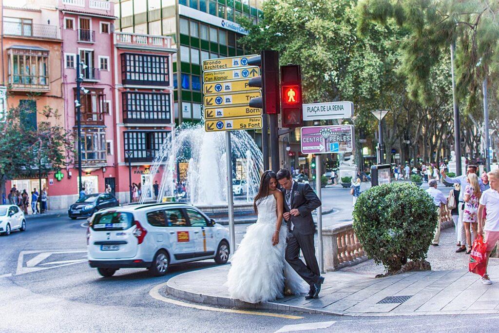 Una pareja de novios que espera a cruzar la calle, apoyados en un semáforo que debe cambiar de rojo a verde en cualquier momento. Un ejemplo típico de Fotografías de Boda Originales de estilo urbano.