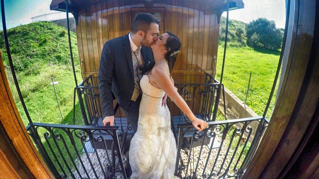 Novios se besan en el balconcillo del vagón de tren mientras circula a velocidad moderada. Fotografías de Boda Originales en el tren de Sóller.