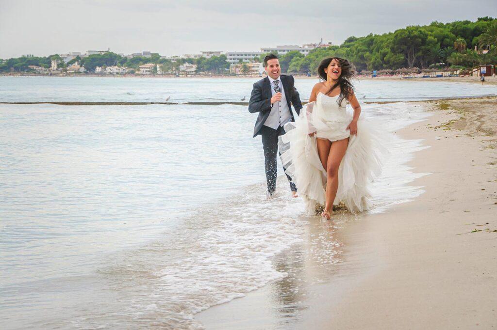 Foto de boda en la Playa de Ca'n Picafort. La novia disfruta feliz corriendo por la orilla levantándose el vestido, mientras es perseguida por el novia a poca distancia.