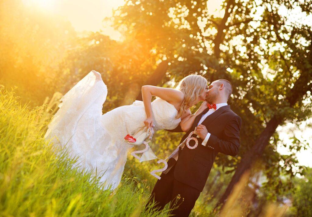 Foto de boda increíble. Esta pareja de recién casados se besa describiendo una imagen diferente y poco habitual. La novia se inclina hacia adelante doblando su pierna derecha hacia atrás. Ambos sostienen los símbolos de su boda. La situación tiene lugar en el campo al atardecer.