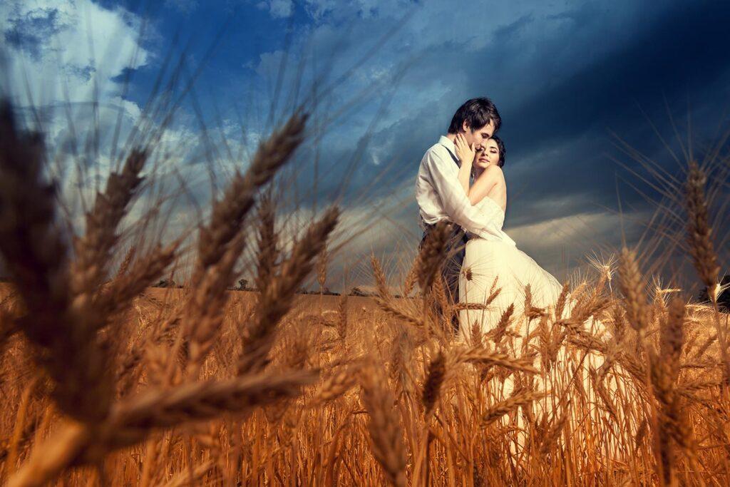 Pareja de novios en campo de trigo bajo un cielo azul dramático.